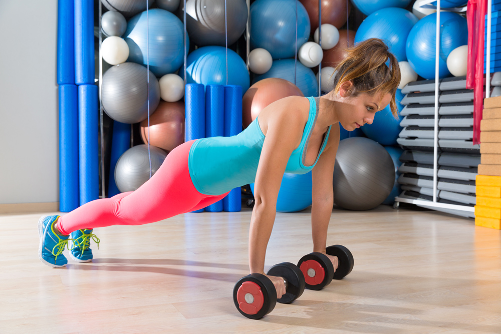Girl at gym push-up pushup exercise dumbbells